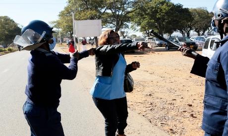 Riot police arrest a nurse in Harare, Zimbabwe