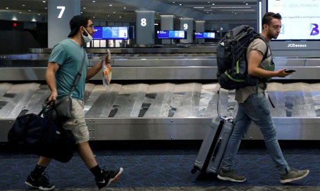 FILE PHOTO: Travelers pass a sign alerting them to distance at LaGuardia Airport, during the outbrea
