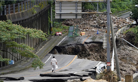 A man walks on heavily damaged road following a heavy rain in Kumamura, Kumamoto prefecture, souther