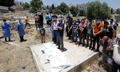 Relatives pray before the body of a Palestinian man who has died after contracting the coronavirus d