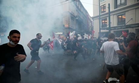 Demonstrators run away from tear gas in Greece