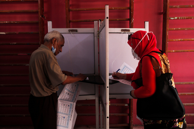 Voters fill out their ballots at a school used as a polling station during Egypt