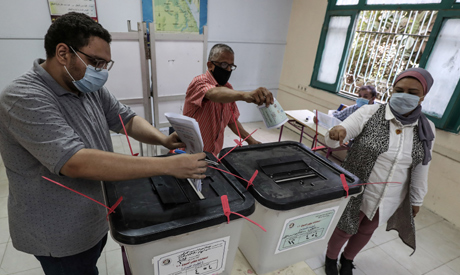 Egyptians, mask-clad due to the COVID-19 coronavirus pandemic, cast their ballots at a pool station