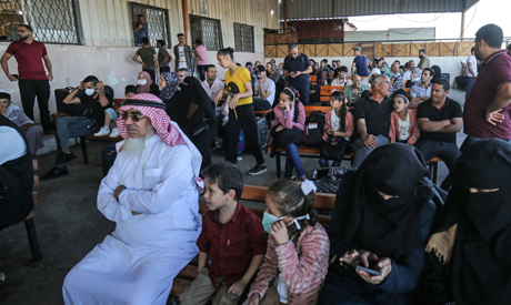 Palestinians wait to cross to the Egyptian side of Rafah border crossing after months of closure due