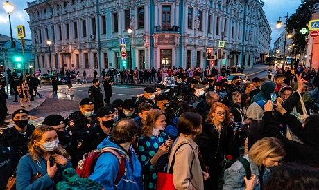 Police officers push protestors outside the Belarusian embassy