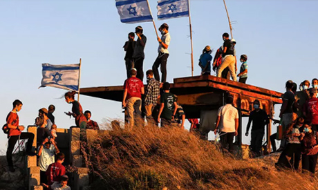 Israeli settlers, some mask-clad, gather on a hill next to the Palestinian town of Halhul, north of