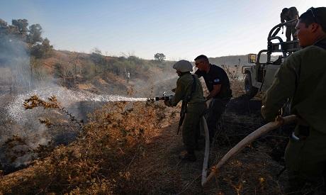 Israeli soldiers extinguish a fire near the kibutz Kissufim