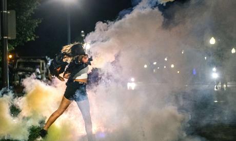 KENOSHA, WI - AUGUST 25: A demonstrator throws back a can of Tear gas on August 25, 2020 in Kenosha,