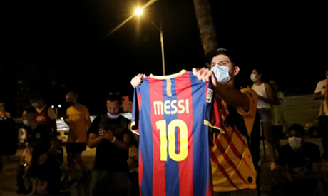 A Barcelona fan holds up a Lionel Messi shirt outside the Camp Nou after captain Lionel Messi told B