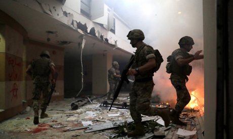 Lebanese soldiers try to extinguihs the flame at the headquarters of the Lebanese association of ban