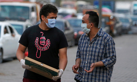 Two Egyptians wearing face masks walk along a street in Shubra El Kheima, El-Qalyubia Governorate, n