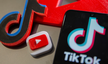 A 3D printed Youtube and Tik Tok logos are seen near smartphone with displayed Tik Tok logo in this