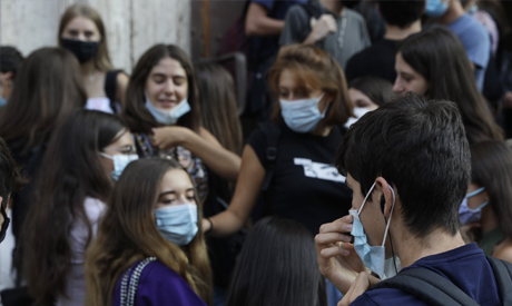 Students gather outside the Visconti high school on the first day of the reopening in Rome, Monday,