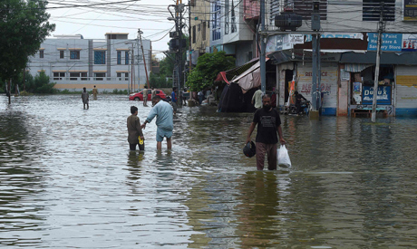 People wade through a flooded residential area following heavy monsoon rains triggered floods in Pak