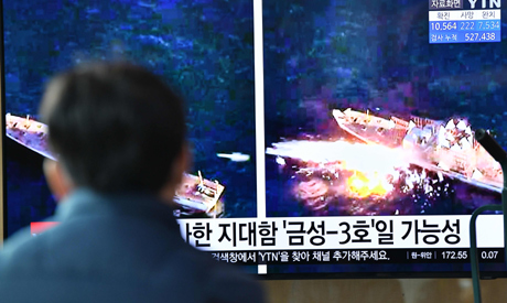 File photo a man watches a television news broadcast showing file footage of a North Korean missile