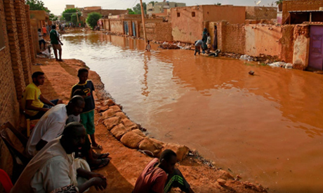 Sudanese residents sit outside their flooded houses in Omdurman, the twin city of the capital of Kha