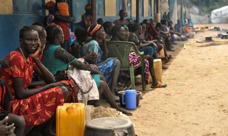 Internally displaced South Sudanese families sit outside a classroom as they shelter from flood wate
