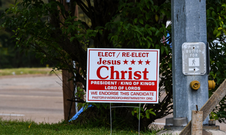 """A sign motivating voters to """"Elect/re-elect Jesus Christ"""" is seen on a roadside near a church in Jac"""