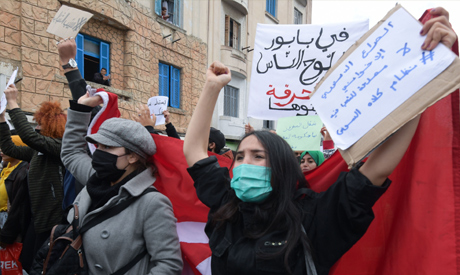 Tunisian protesters lift placards and national flags during an anti-government demonstration in the