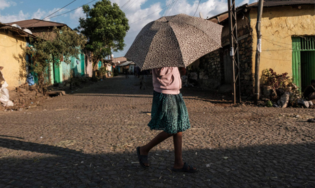 A woman walks with an umbrella in the city of Gondar, Ethiopia, on January 17, 2021. AFP