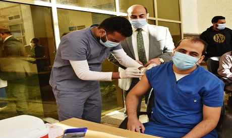 A member of the Egyptian medical staff receives his first dose of the Chinese Sinopharm vaccine (Pho