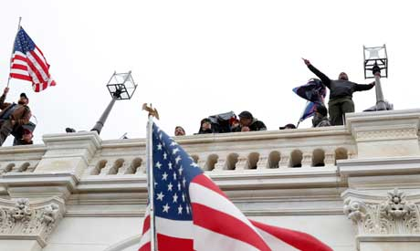 Pro-Trump protesters wave American flags after breaching the Capitol barricades during a rally to co