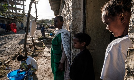 Displaced people from Tigray stand at the door of a classroom in the school where they are shelterin