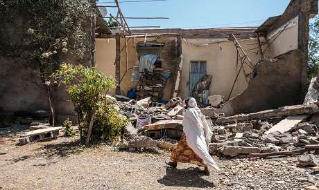 Ethiopian woman walks in front of a damaged house Mekele. AFP