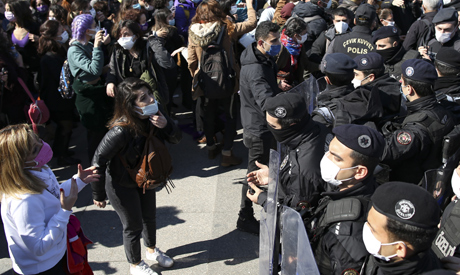 Protesters, left, confront Turkish police officers forming a barricade during a demonstration in Ist