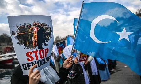 Members of Women Muslim Uighur minority hold placards and flags of east Turkestan AFP