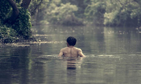 An Indonesian man swims at a natural pool where Javanese Muslims perform Padusan