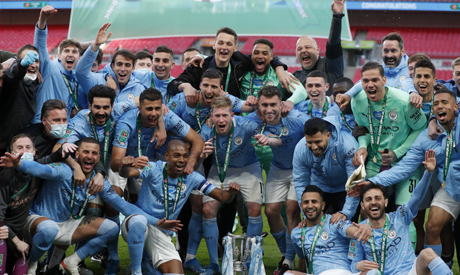 Manchester City players celebrate with the trophy at the end of the English League Cup final soccer