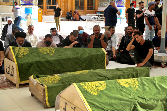 Mourners pray near the coffins of coronavirus patients who were killed in a hospital fire, during th