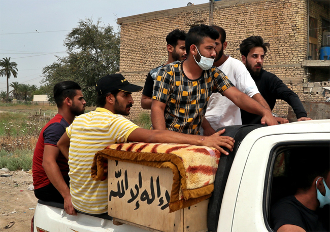 Mourners take the body of Khudair Ali, a coronavirus patient who died in a hospital fire, during his
