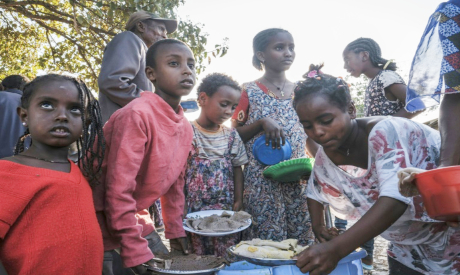 Displaced children receive plates of food outside a classroom in Tigray region