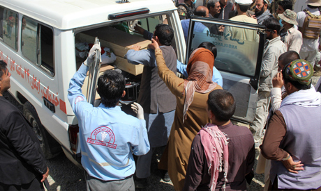 Afghan men transfer a coffin of a victim of last night