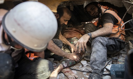 Rescuers pull the body of a woman from under the rubble of a destroyed building in Gaza. AP