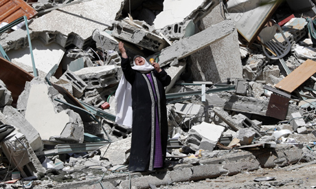 A woman reacts while standing near the rubble of a building that was destroyed by an Israeli airstri