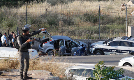 An Israeli border policeman stands guard on May 16, 2021 at the scene of a car-ramming attack which