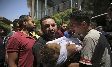 A relative reacts carrying body of a Palestinian child who was killed in Israeli airstrikes in Gaza.