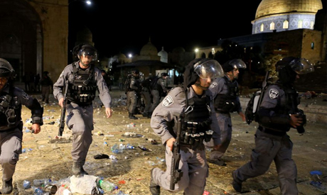 Israeli police run during clashes with Palestinians at the compound that houses Al-Aqsa Mosque, know