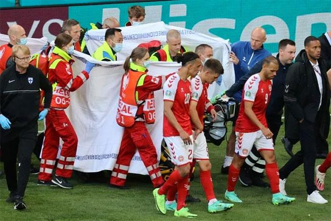Players escort paramedics as Denmark