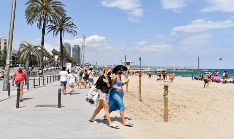 People walk on the promenade at Barceloneta Beach in Barcelona,  Spain. AFP