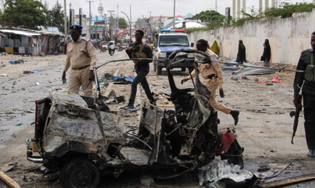 Police officers patrol by the wreckage of a car at the scene of suicide car bomb attack that targete
