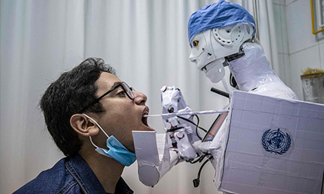 A prong extending from a remote-controlled robot prototype approaches the mouth of a volunteer to ex