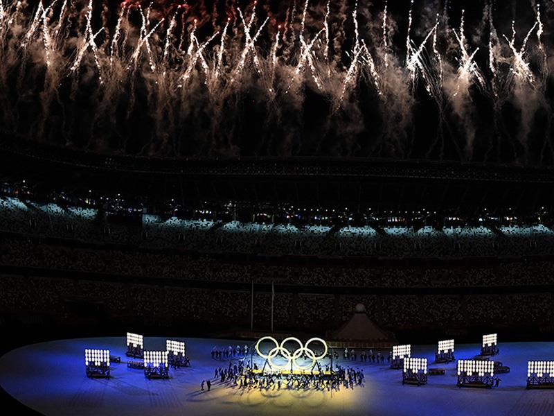 Performers assemble the Olympic Rings as fireworks go off overhead during the opening ceremony of th