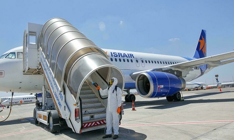 File photo: An Israeli worker in full hazmat suit sprays disinfectant on the stairs of an Israir air