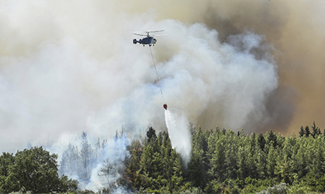 A helicopter pours star on wildfires in Kacarlar village near the Mediterranean coastal town of Mana