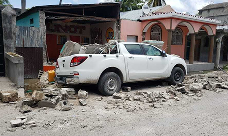 A truck is covered by parts of a wall that fell on it during an earthquake in Les Cayes, Haiti, Satu