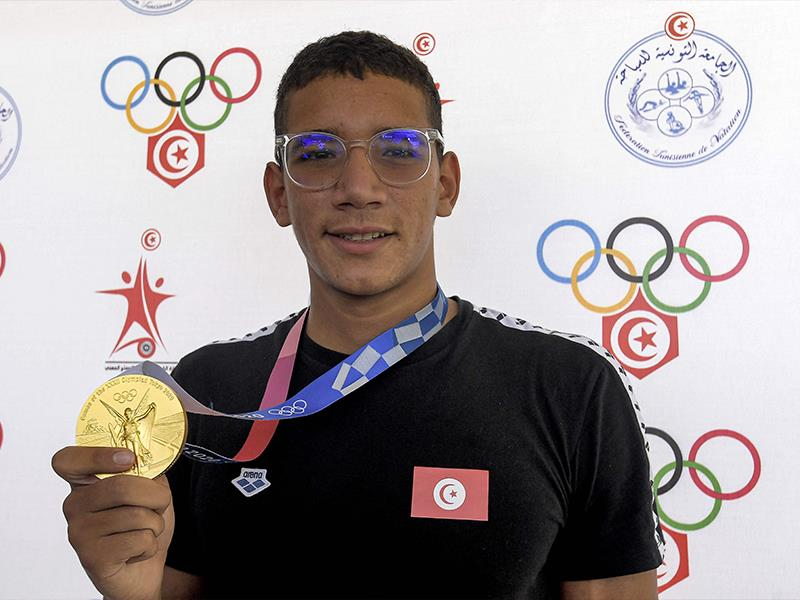 Tunisia s Gold medalist swimmer Ahmed Hafnaoui poses with his medal as he arrives at Tunis-Carthage